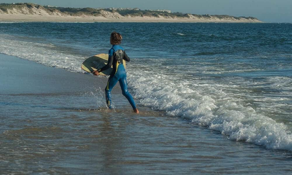 A young boy skimboarding