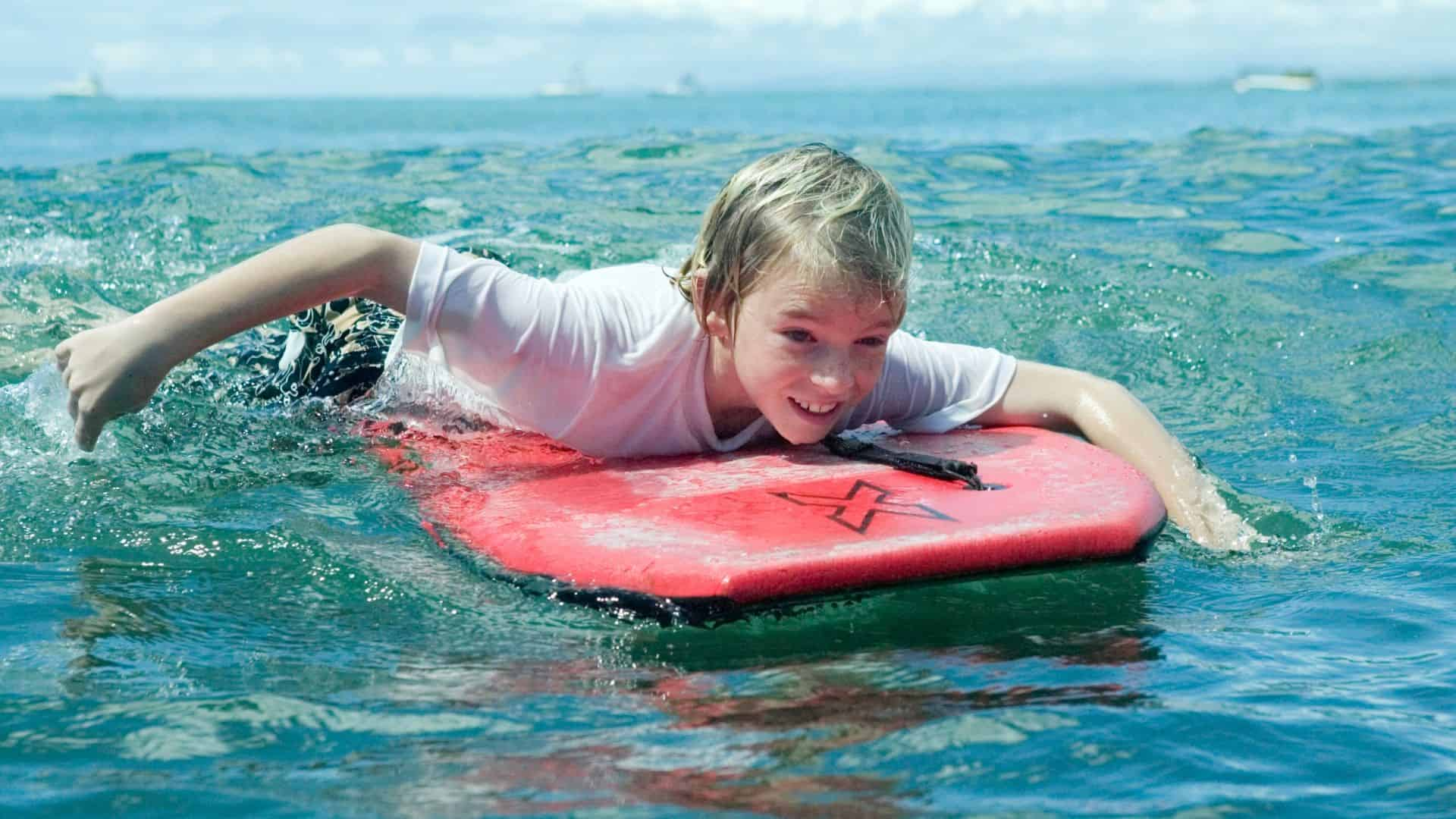 A young boy bodyboards in the surf.