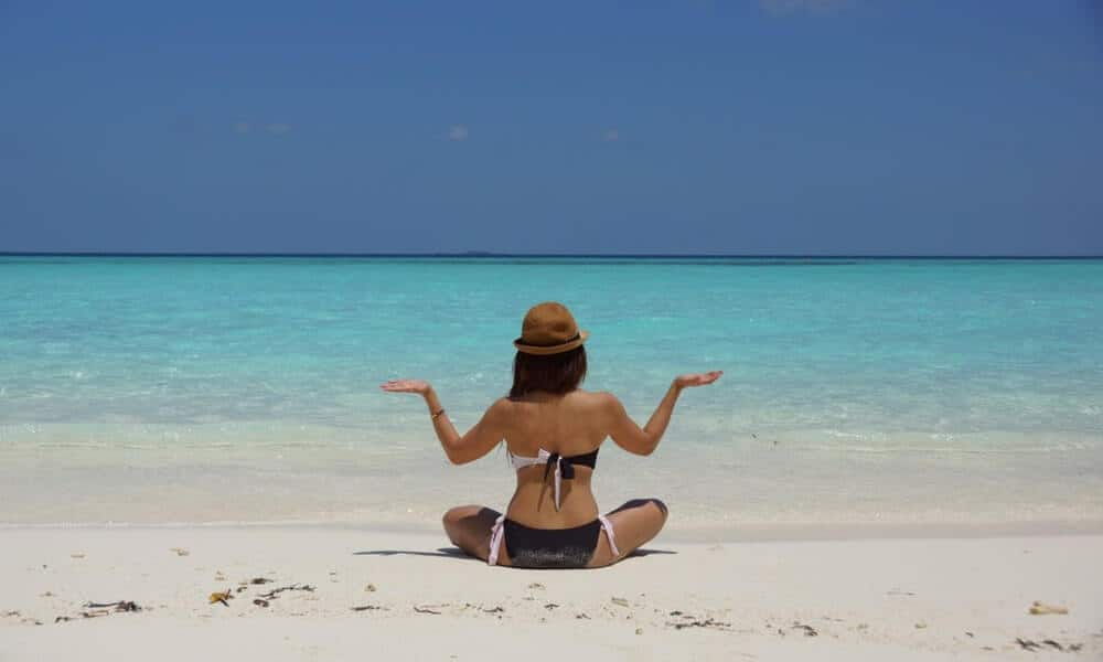 A woman doing yoga on the beach