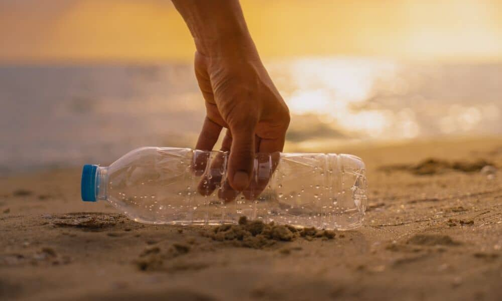 picking up a plastic bottle from the beach
