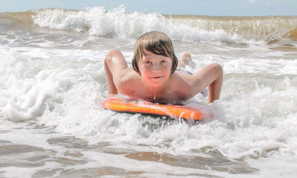 young boy bodyboarding in the ocean