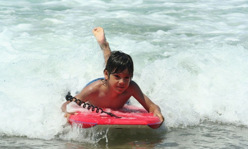 young boy bodyboarding