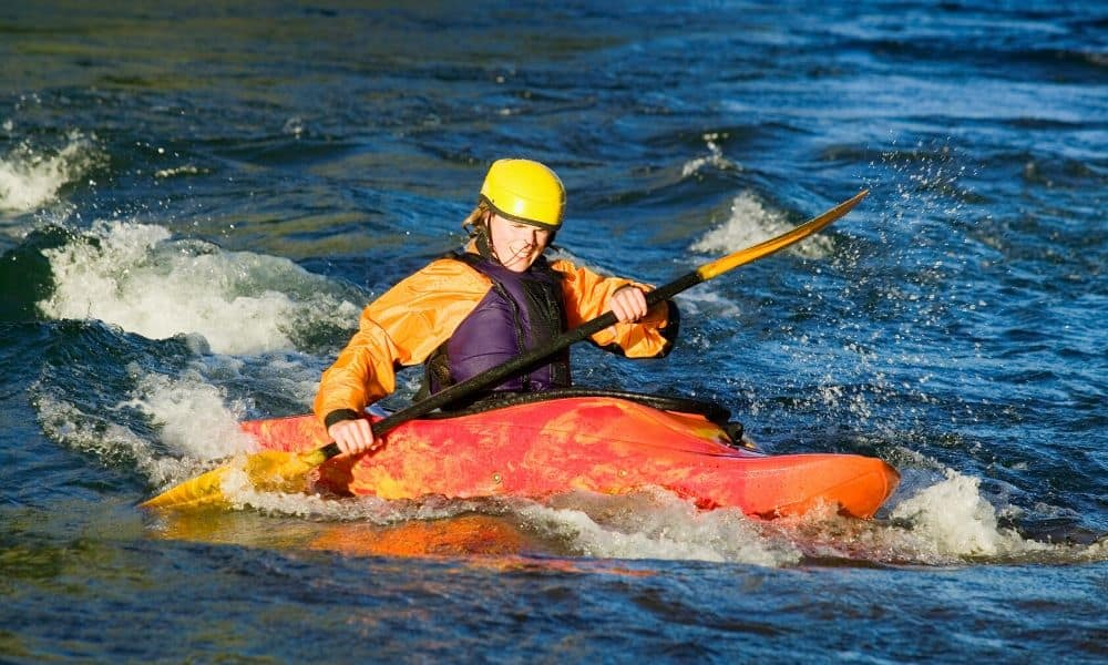 kayaker paddling in rapids
