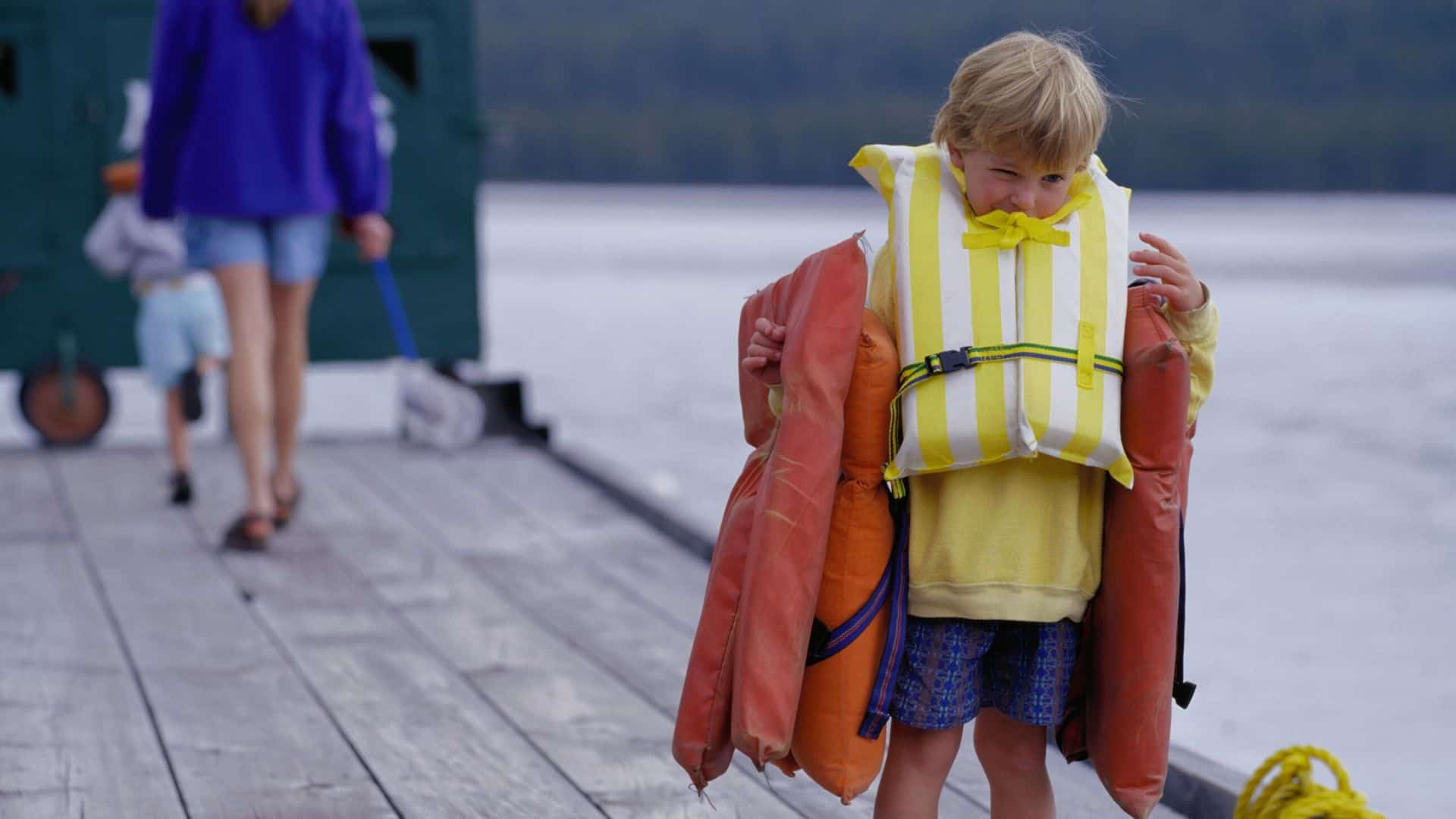 young boy carrying life jackets
