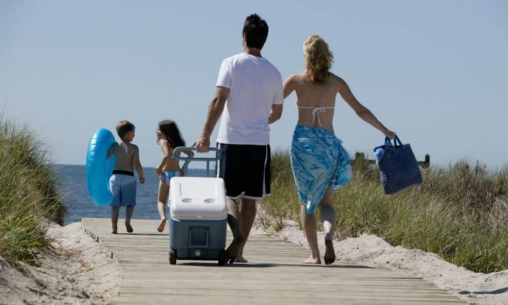 family carrying gear to the beach
