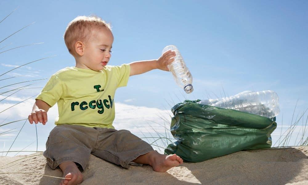 toddler putting plastic bottle in a bag