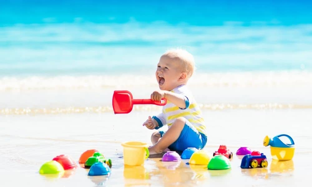 baby playing with beach toys