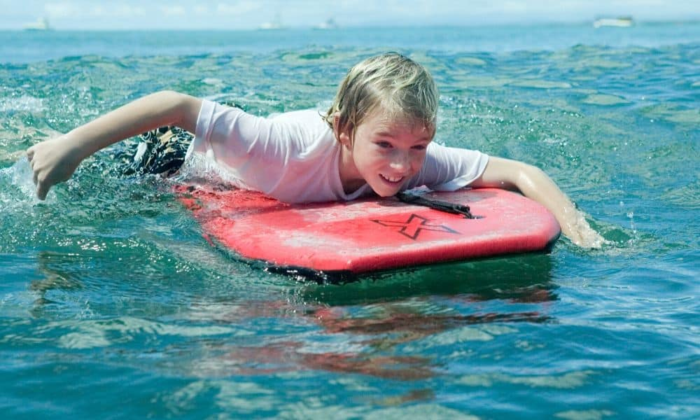 boy paddling a bodyboard