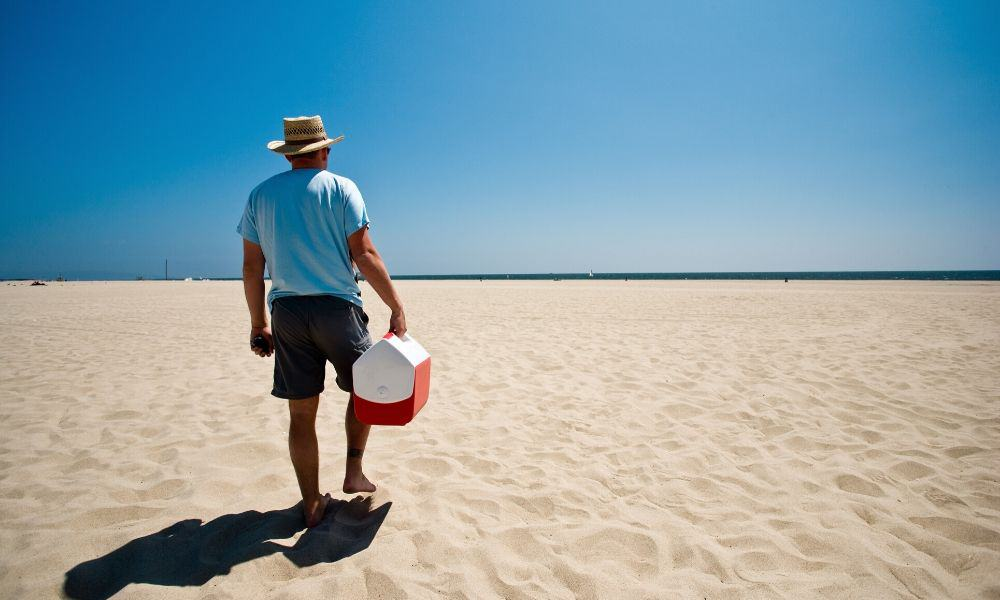 man carrying a beach cooler