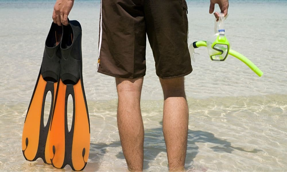 man carrying snorkeling fins