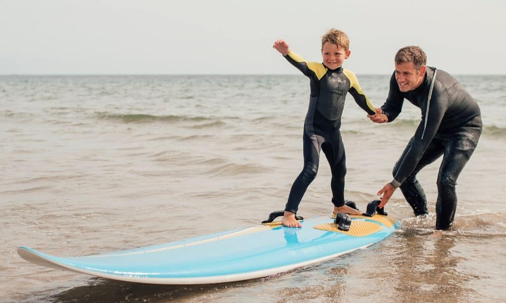 Dad teaching his son to surf