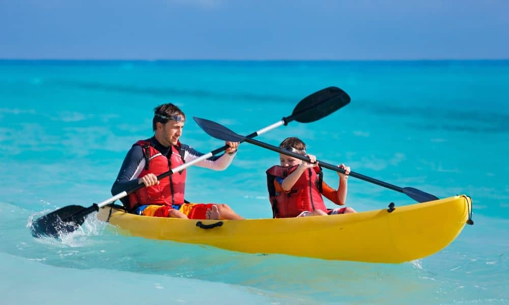 father and son in sit on top kayak