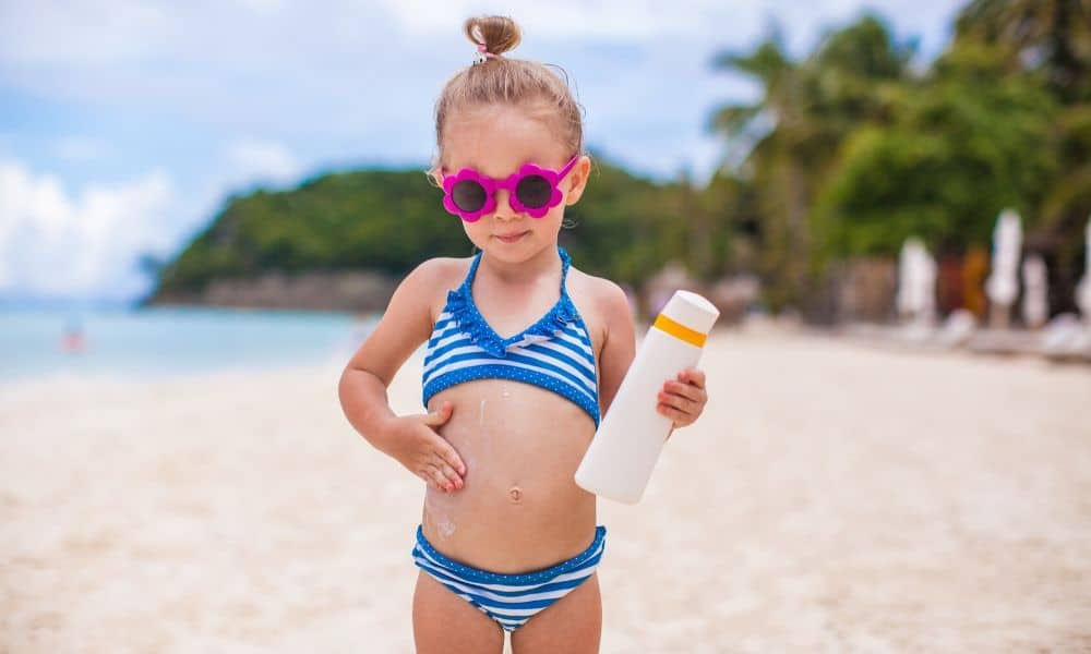 little girl applying sunscreen