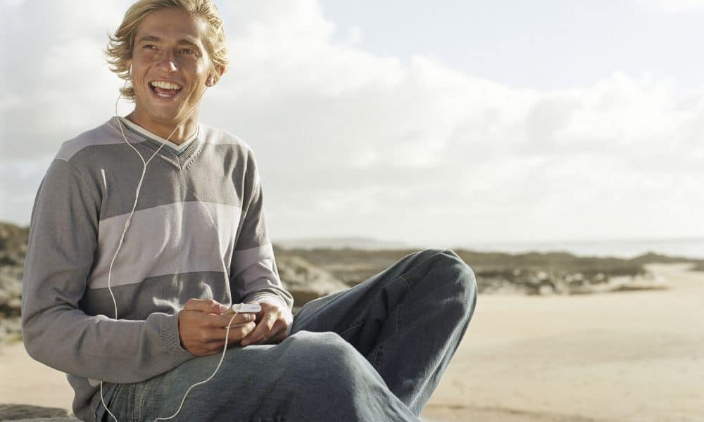 man listening to music at the beach