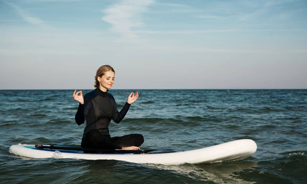 woman doing yoga on a paddleboard