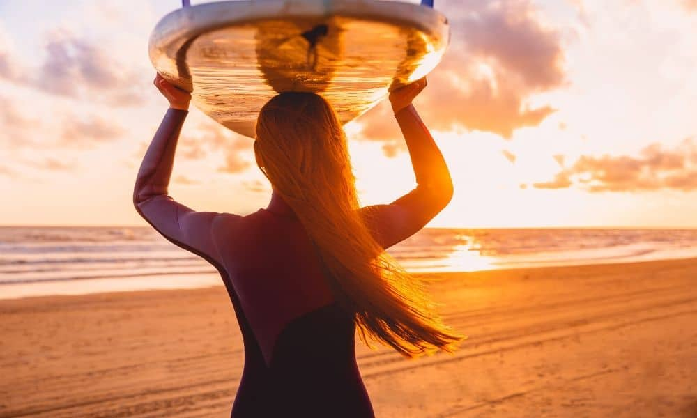 woman with surfboard at dawn